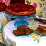 A fruit tart on a cake stand with brownies, pecan bars and frosted cookies