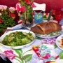Table setting of a caesar salad and ravioli along with a loaf of bread and knife