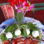 Prosciutto with basil and balls of Mozzarella and a vase of flowers