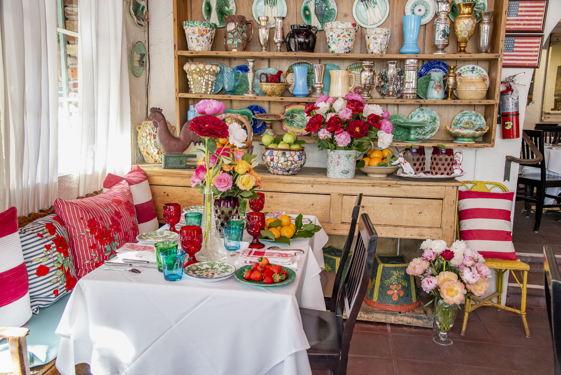 The Ivy Restaurant main room interior, facing an antique Welsh cupboard whos shelves are filled 